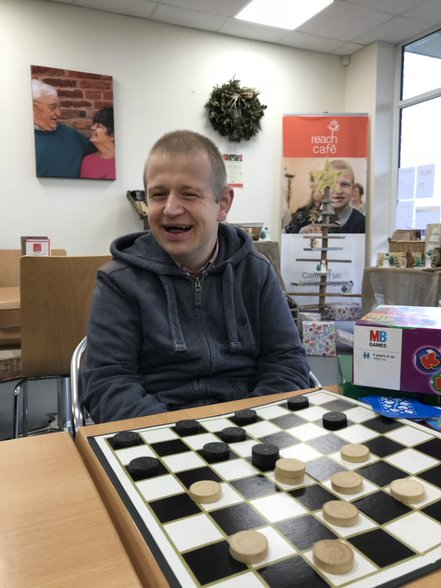 Picture of man playing draughts and smiling