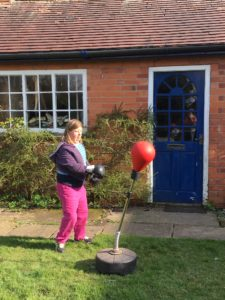 Picture of Bex hitting a punch bag in her garden