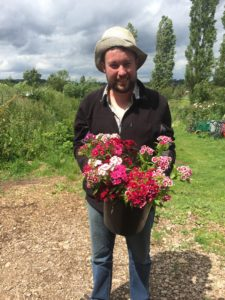 Picture of Alasdair holding some flowers and smiling