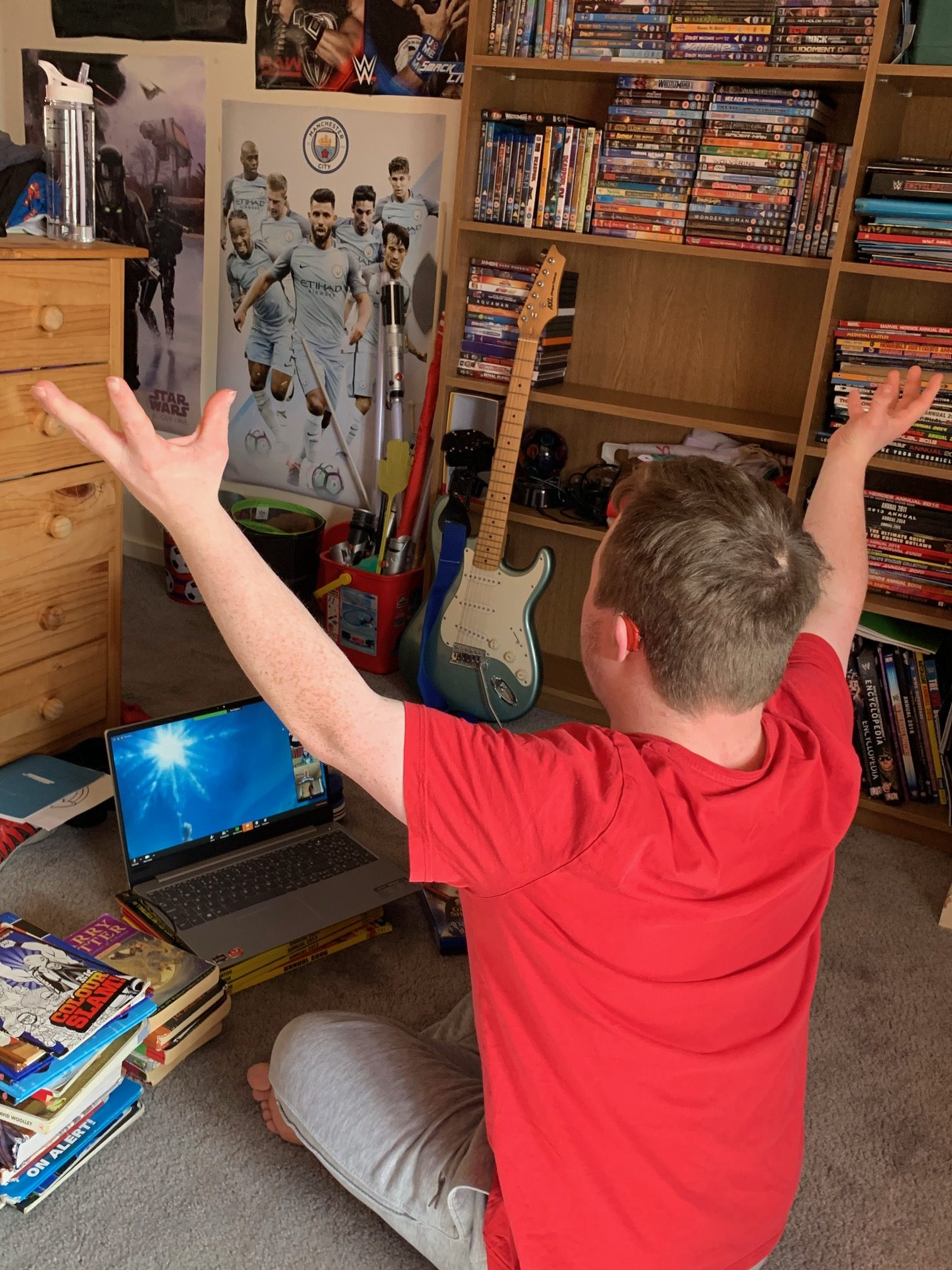 James looking at a laptop with his hands in the air