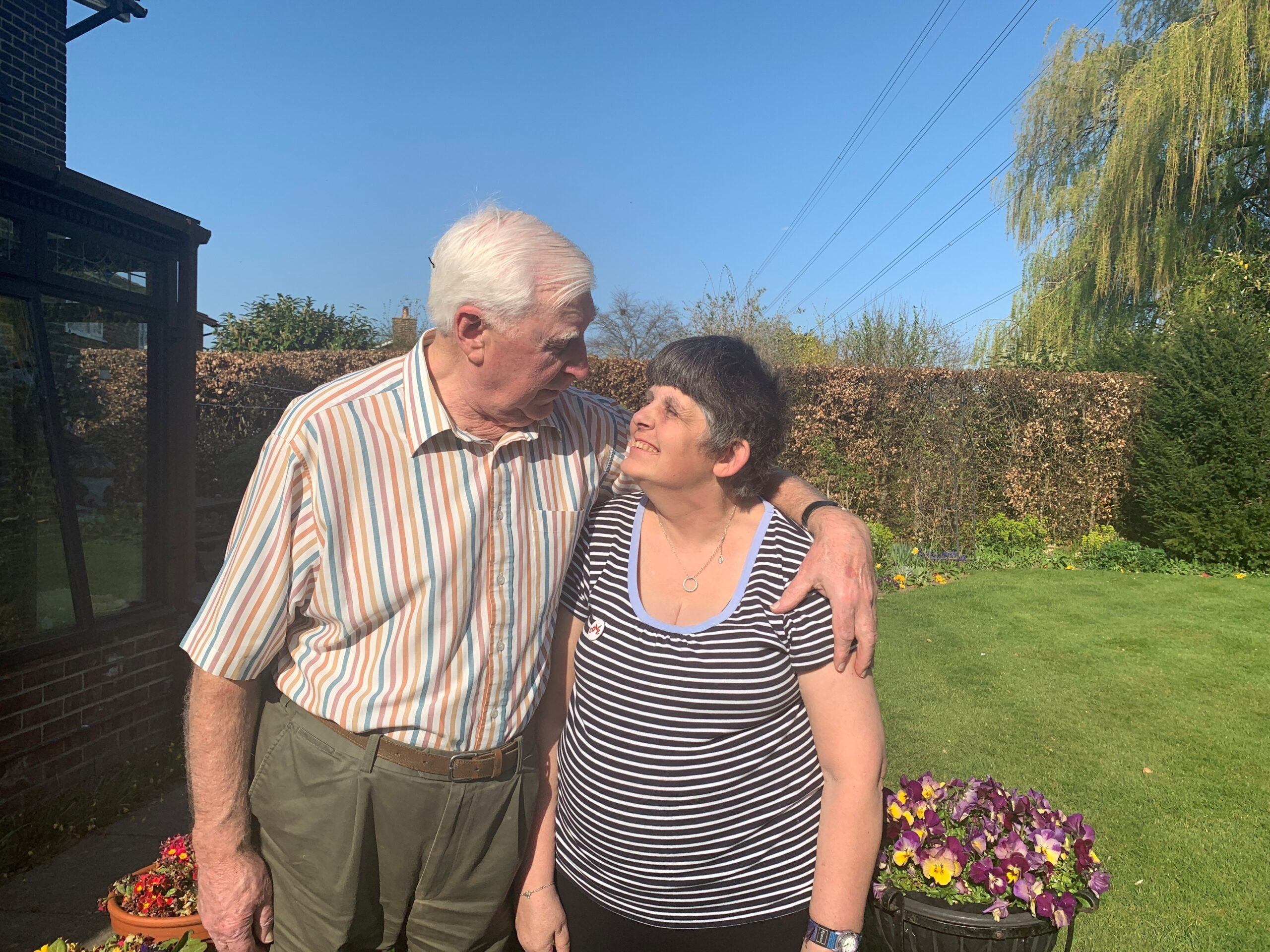 Photograph of Peter and Sarah in the garden smiling at each other