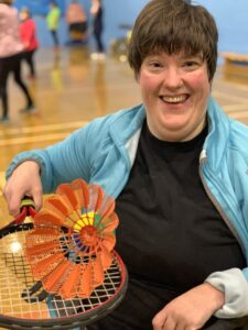 Chelsea holding a badminton racket and smiling
